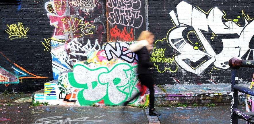 Women walks past bright blue graffitti on a housing estate in Manchester